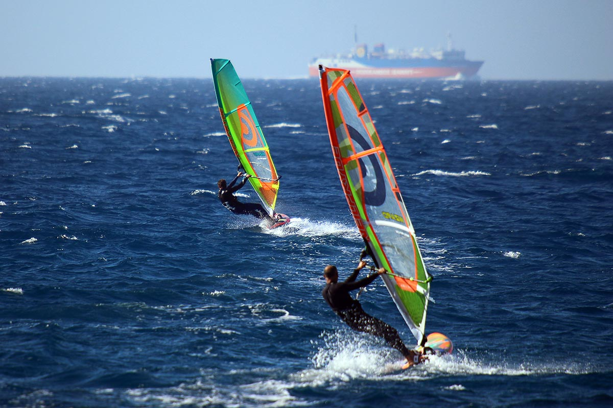 windsurfers blasting over blue water